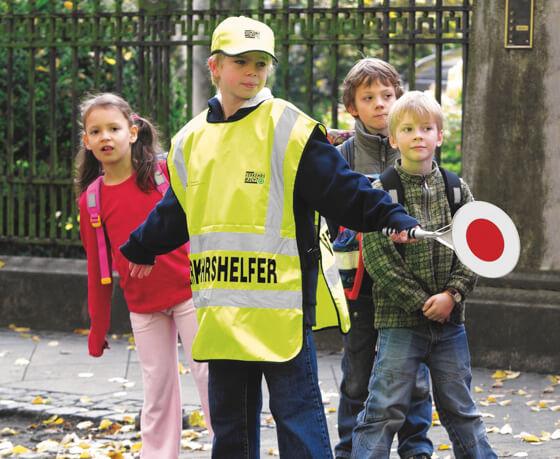 Verkehrshelfer hilft Schülern über die Straße zu kommen